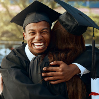 Portrait of a happy young man and woman hugging on graduation day.