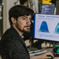 Male researcher in lab showcasing latest research statistics on computer
