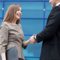 Successful business people shaking hands for greeting or in agreement happy to work together. Focus on smiling businesswoman.