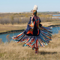 Indigenous woman dancing is colorful shaw on top of hill overlooking river