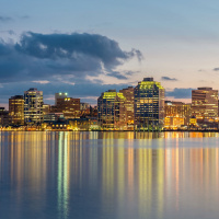 Panoramic Skyline of Halifax City illuminated at night reflecting in the water of Halifax harbour.