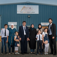 Tareq Hadhad, owner of Peace by Chocolate, standing proud in front of the store front with his Syrian family.