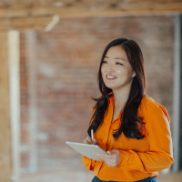 Young Chinese woman holding tablet in middle of modern design agency